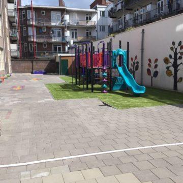 Kleurrijk schoolplein met bankjes en groot klimtoestel met twee glijbanen op kunstgras - Klimtoestellen met glijbaan - Speeltoestellen