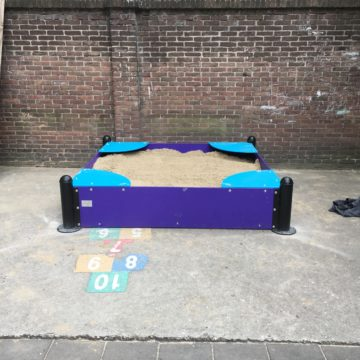 Zandbak van gekleurde PE platen tegen een muur aan - XYZ Fantasia - Speeltoestellen - LuduQ speeltoestellen