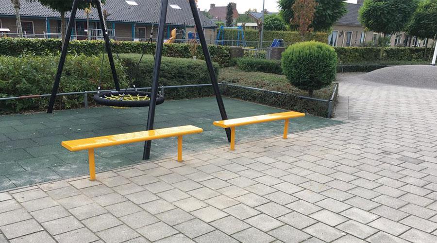 Twee gele roestvrij stalen bankjes op schoolplein voor een schommel - Straatmeubilair - Sport en spel - LuduQ speeltoestellen