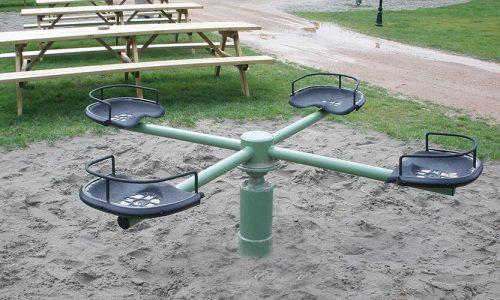 Groen draaitoestel met vier zittingen in zand geplaatst - Draaitoestellen - Speeltoestellen - LuduQ speeltoestellen