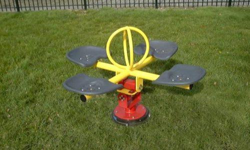 Gele tuimelaar op grasveld - Veer- en wipelementen - Speeltoestellen - LuduQ speeltoestellen